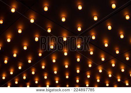 A ceiling with myriad glowing yellow lightbulbs