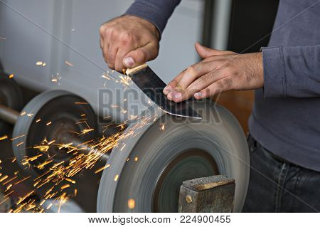 Man Hands Sharpening The Knife With Sparks Flying Out.