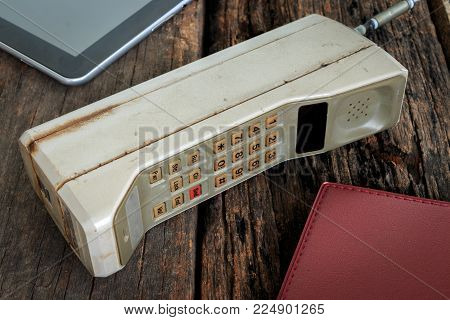Old mobile phone put on wooden table ,Vintage tone style.