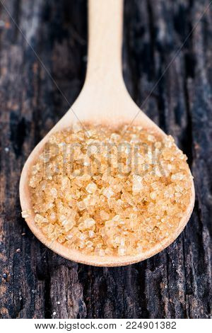 Close up sugar in wooden spoon on wooden table