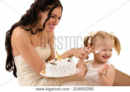 happy mother and daughter eating cake on birthday isolated on white