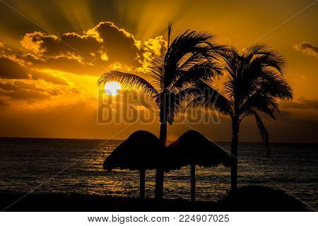 Warm sunrise with palm trees and palapas in the foreground. Riviera Maya Mexico.