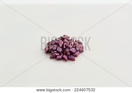 a pile of small irregular shaped purple beads that are used to create jewelry