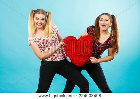 Happy two teenager women holding heart shaped pillow. Valentines day gift ideas, teenage love concept.
