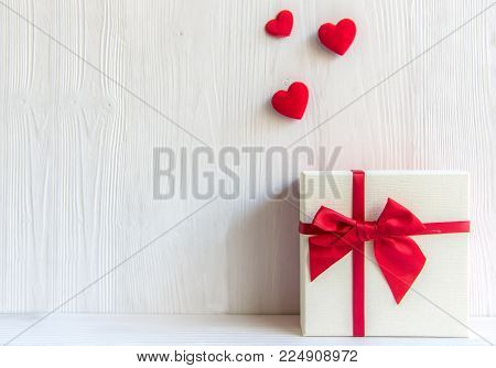 Valentines day white gift box with a red bow on white wall background, copy space. Valentine Concept.