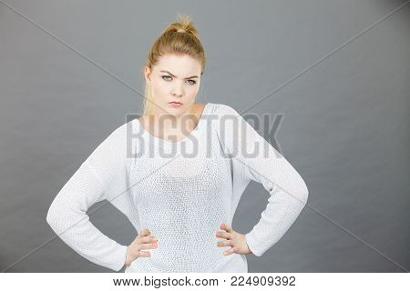 Confused young blonde woman looking suspicious. Confusion face expressions concept. Studio shot on grey background.