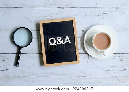 Top view of magnifying glass,a cup of coffee and blackboard written with 'Q&A' on white wooden bakground.