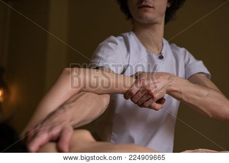 Proffessional Masseur Stretches Hand of Youn Woman at Abyanga Massage Session. Close up