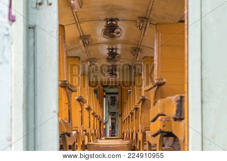 Inside of old public Thai railway train cabin with seats, handrails, fan and interior in vintage style service for passenger transport