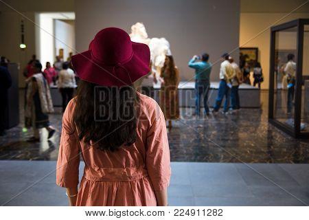 ABU DHABI, UNITED ARAB EMIRATES - JANUARY 26, 2018: Female tourist visiting Louvre in Abu Dhabi, United Arab Emirates