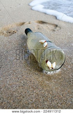 A transparent glass bottle with adhering seashells on a sandy beach. Footprints in the sand. Waves