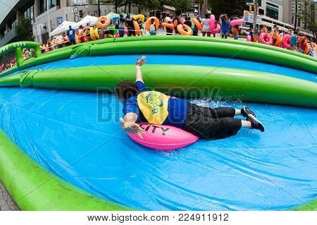 ATLANTA, GA - JULY 2017:  A woman joyfully rides an innertube down a giant water slide on a city street, at the Slide The City event in Atlanta, GA on July 15, 2017.