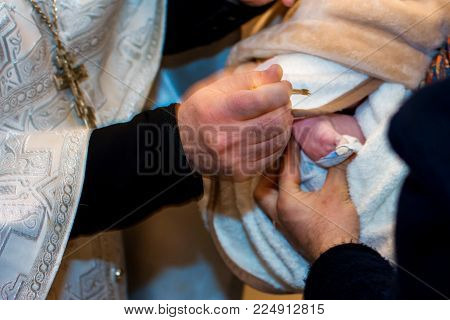 Chrismation sacrament of newborn baby during christening baptism with hands of orthodox priest