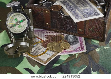 A casket, a chest of coins, old banknotes and a compass on camouflage cloth, a search for rare finds. The concept of adventurers and treasure hunters. Theme for computer games loot box.