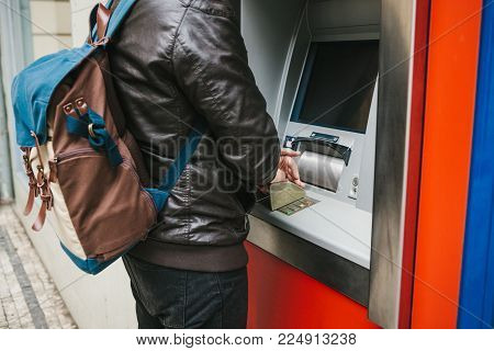 The tourist withdraws money from the ATM for further travel. Credit card, withdrawal of money. Dials the code with one hand and closes the buttons with the other hand to protect the information.