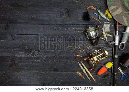 Fishing rods and reels, fishing tackle on black wooden background