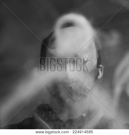 Young Man with Beard and Mustages Vaping an Electronic Cigarette. Vaper Hipster Smoke Vaporizer and Exhals Smoke Rings.