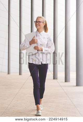 A young business woman or perhaps a student walking with her laptop. Picture was taken in Gran Canaria, Spain