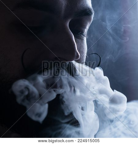 Young Man with Beard and Mustages Vaping an Electronic Cigarette. Vaper Hipster Smoke Vaporizer and Exhals Smoke Flow from Nose.