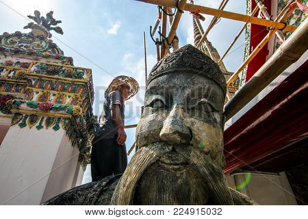 Bangkok, Thailand Noverber 29, 2017 : A repairman is repairing a roof in Wat Pho with a giant statue in front. (Chinese style sculpture and thai art architecture in Wat Phra Chetupon Vimolmangklararm (Wat Pho) temple in Thailand )