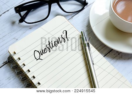 Pen,a cup of coffee and notebook written with 'QUESTIONS?' on white wooden background.