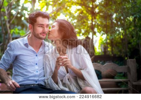 Romantic Concept.  Asian women and man happiness and romantic scene of love couples partners making eye contact and kiss in the garden at home for valentine day.