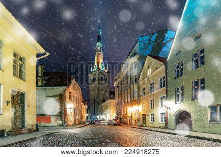 Night snowy street and St. Olaf Baptist Church illuminated of Medieval Old Town in Tallinn, Estonia