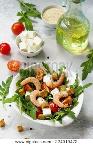 Festive appetizer. Salad with shrimps, feta cheese, arugula, cherry tomato and sesame on a stone or slate background. Top view.