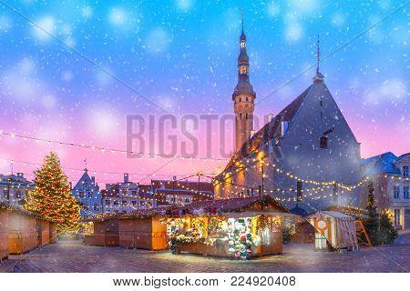 Decorated and illuminated Christmas tree and Christmas Market at Town Hall Square or Raekoja plats at beautiful snowy sunrise, Tallinn, Estonia.