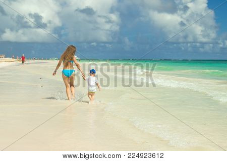 Mum And Son Are Walking Along The Beach.