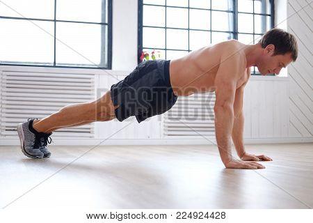 Shirtless middle age man doing push ups.