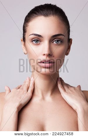 closeup studio portrait of young beautiful brunette woman with hands on her neck and clean fresh skin isolated on light grey studio background