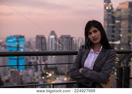 Business Concept. Asian businesswoman looking at book. Young businesswoman is happy to read. Young businesswoman reading a book on the top of a building in the evening.