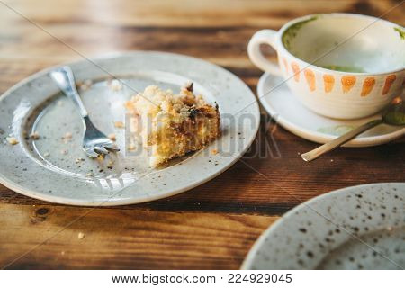 A dirty plate and an empty cup of coffee. The half-eaten cupcake on a plate. Empty dishes after eating