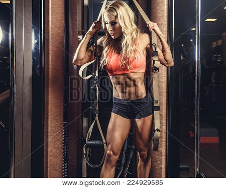 Sexy blond female doing workouts with trx fitness strips in a gym club.