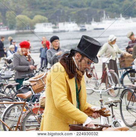 Stockholm - Sept 23, 2017: Elegant Upper Class Gentleman With Bicycle Dressed In Yellow Overcoat And