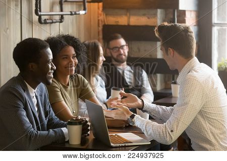 Insurance salesman or mortgage broker consulting young african american couple in cafe, caucasian realtor making offer explaining deal details to smiling black customers at meeting in coffee house