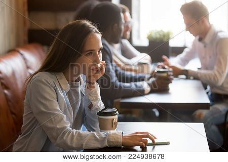 Pensive upset young rejected girl waiting for boyfriend to come on first date in cafe, frustrated social outcast or loner sitting alone at coffeeshop table with phone offended excluded by friends
