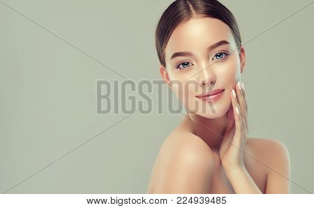 Beautiful young woman with clean fresh skin  .Girl  beauty face care. Facial  treatment   . poster