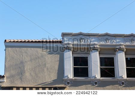 Roofline of a building with both plain stucco and ornamental window facing, terra cotta tile roof, copy space, horizontal aspect