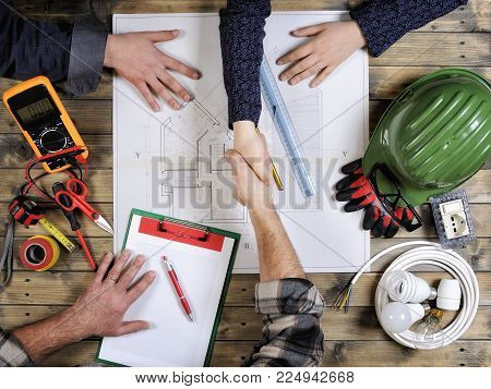 top view of young engineers and a technician studying a residential construction project on an antique wooden table