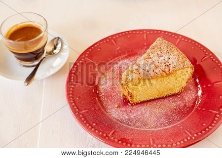 Homemade pie on a ceramic plate on a white wooden table. A piece of delicious carrot pie on a red shiny plate. Part of a homemade cupcake on a plate with black coffee.