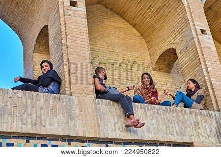 Isfahan, Iran - April 24, 2017: A young man talks to the girls, sitting on an arched niche of a stone bridge.