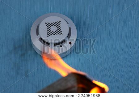 white smoke detector on a blue wall and a fire