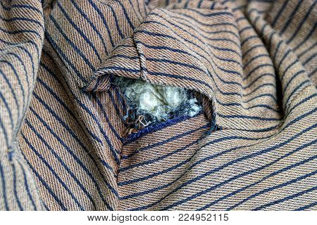 tattered hole on brown striped old clothes