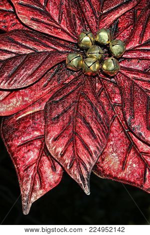 Close-up of a glistening, sparkling red Christmas artificial poinsettia ornament with central golden jingle bells used as decoration on black background.