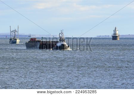 New Bedford, Massachusetts, USA - February 2, 2018: Tug Kodiak towing barge toward New Bedford harbor from Buzzards Bay followed by trawler Boomer Too