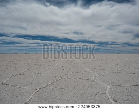 Tires tracks left by tour vehicle on the salty surface of Salar de Uyuni, Bolivia.