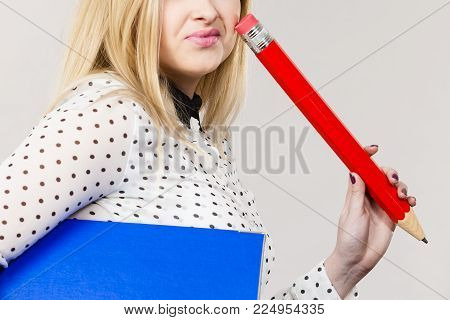 Woman holding binder with many documents and pen. Office, bookkeeping objects concept, on grey