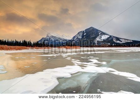 Winter sunrise over a frozen Vermilion Lakes in Banff National Park with snow-capped Mount Rundle in the background and pine tree silhouette along the shoreline. HDR rendering.